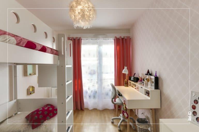 Une chambre deux enfants grâce à une mezzanine pour optimiser au maximum l'espace et agrandir l'espace de jeu. Toujours un coin bureaux pour les moments studieux et surtout un peu de sérieux dans ce bel univers rose/rouge.