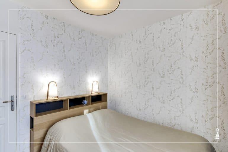 Zoom sur la chambre dans les tons beige boisé. Un papier peint blanc à motif discret pour un style épuré en toute simplicité.