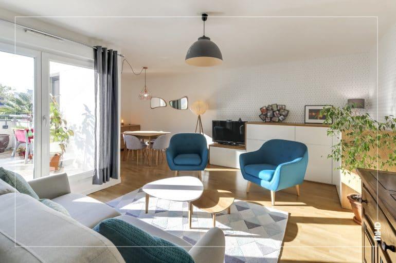On observe sur cette photo un beau séjour sublimé par la lumière entrante par le balcon. En second plan, on retrouve en transparence la cuisine agencée en pièce à part grâce à la belle verrière. Dans les tons gris, bleu et beige, un style scandinave et épuré pour cette belle pièce de vie. On peut également voir le travail fournis par nos architecte sur la création d'un meuble sur mesure s'intégrant parfaitement dans ce salon.