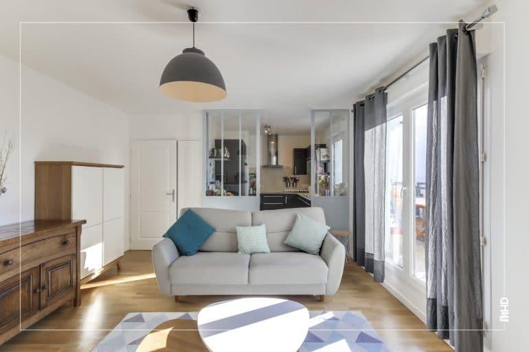 On observe sur cette photo un beau séjour sublimé par la lumière entrante par le balcon. En second plan, on retrouve en transparence la cuisine agencée en pièce à part grâce à la belle verrière. Dans les tons gris, bleu et beige, un style scandinave et épuré pour cette belle pièce de vie.