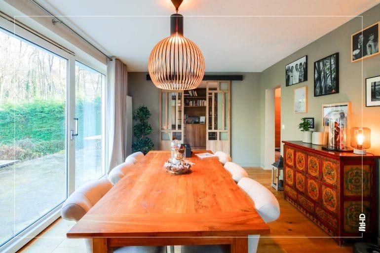 On observe une salle à manger très lumineuse grâce aux portes coulissantes pensées et dessinées sur mesure permettent de cloisonner l'espace sans perdre en luminosité. Une belle table en bois brute mise en valeur par ce magnifique luminaire.