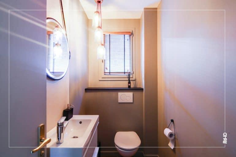 Une pièce assez grande dédiée aux toilettes qui permet d'avoir un lavabo et un miroir sublimé par trois luminaires intimistes et chaleureux.