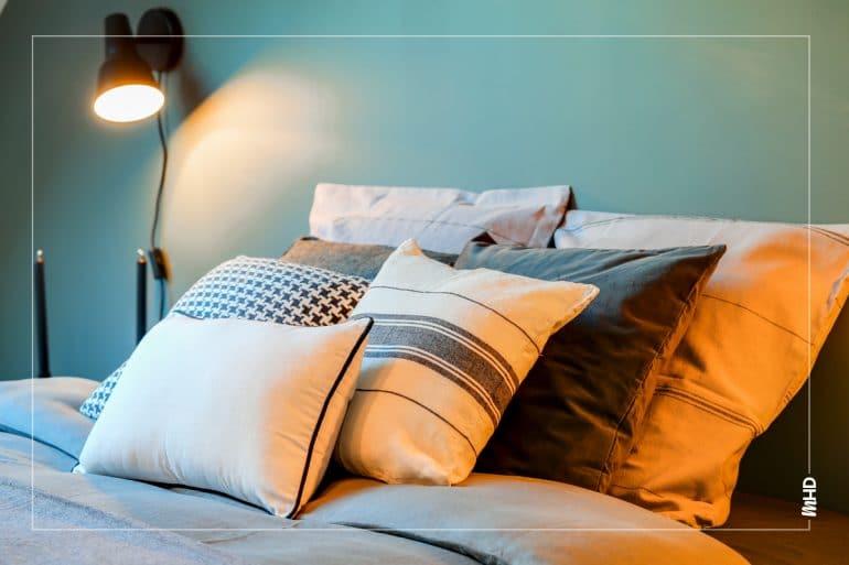 Zoom sur le lit: une superposition de coussins toujours dans ces même couleurs chic et noble.