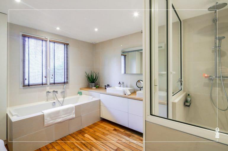 La salle de bain a été conçue comme une cabine privée d'un spa avec au sol un parquet bateau, une douche XXL, un meuble vasque dessiné et réalisé sur mesure (plateau en chêne massif) qui fait la jonction entre la douche et le bain. La baignoire quant à elle à été positionnée pour avoir une vue parfaite sur la forêt.
