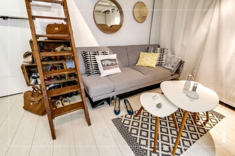 Zoom sur le coin salon: Dans les tons gris clair et bois, ce petit salon situé au dessous du coin chambre sous mezzanine avec des touches de bois que l'on retrouve sur les pieds de table et l'échelle permettant l'accès à la chambre.