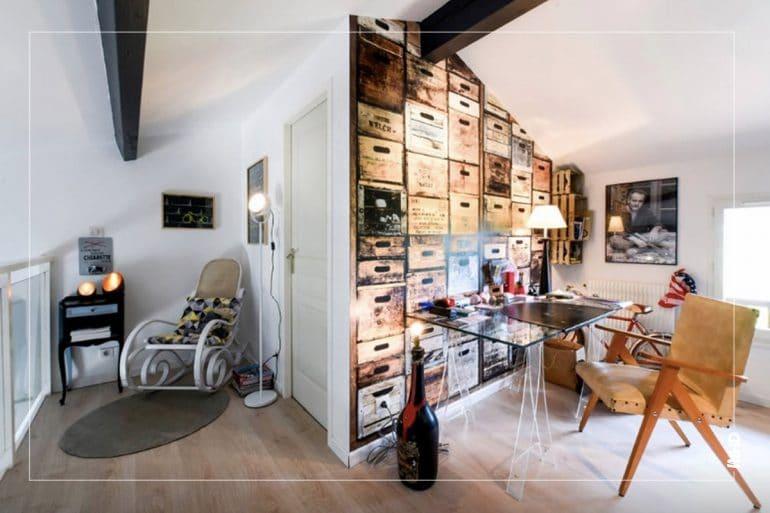 Zoom sur le coin bureau à l'étage. Utilisation d'un papier peint trompe l'oeil. On retrouve deux espaces distincts, un plus cocooning avec un fauteuil et des luminaires pour un moment de lecture et de calme. L'autre côté de la pièce est davantage dédié au travail.