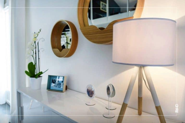Focus sur les détails de décoration du meuble du salon, luminaire, miroir, plantes et photos.