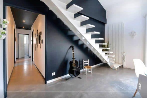 On observe sur cette photo Le grand mur principal a été peint en noir légèrement bleuté (comme les verrières, les poutres apparentes et le plafond du couloir), et accueille désormais le nouvel escalier fait sur mesure, peint en blanc pour contraster avec le mur foncé. Le mur derrière le bureau accueille un superbe papier peint effet caisses en bois vintage, et fait face à celui noir bleuté derrière l'escalier, pour créer un véritable cocon.