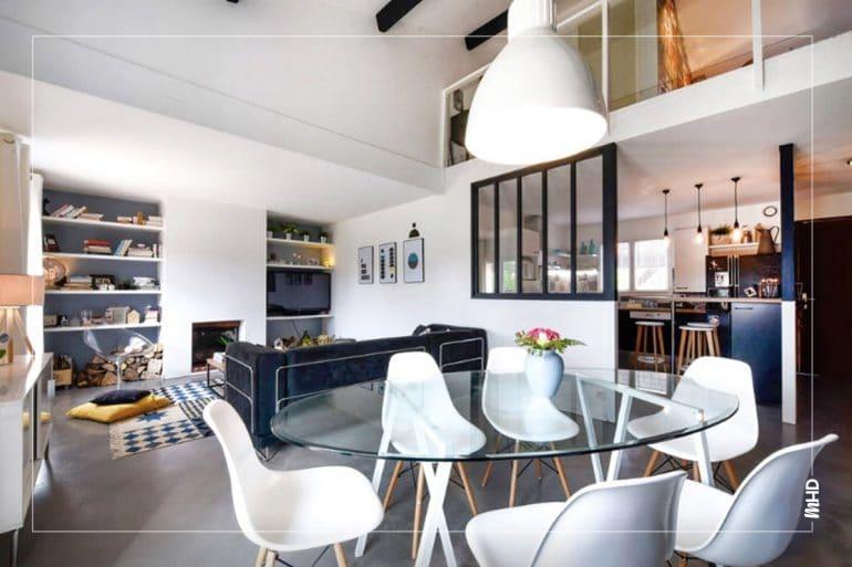 Sur cette photo, nous avons en premier plan une salle à manger moderne avec table en verre mettant en avant ces belles chaises blanche dans un style scandinave laissant apparaître le salon en second plan et la cuisine derrière la verrière sur le côté gauche de la photo. Cuisine : Afin de respecter le budget alloué, nous avons choisi de la relooker plutôt que de concevoir et faire poser une nouvelle cuisine. Nous avons repeint les meubles bas en noir et ceux du haut en blanc, repeint le réfrigérateur en peinture ardoise, créé un ilôt central en détournant 2 meubles hauts qui étaient auparavant de chaque côté de l'ancienne hotte, changé la hotte, l'évier, la robinetterie, posé des étagères, etc, pour donner un vrai coup de jeune. Tout cela sublimé grâce à une nouvelle crédence graphique et un nouveau plan de travail effet bois. Salle à manger / Salon : Le grand mur principal a été peint en noir légèrement bleuté (comme les verrières, les poutres apparentes et le plafond du couloir), et accueille désormais le nouvel escalier fait sur mesure, peint en blanc pour contraster avec le mur foncé. Le coin salon a été rehaussé pour créer un grand espace homogène, la vieille cheminée en pierre a été coffrée pour lui donner un style contemporain et des étagères réalisées sur mesure l'encadrent de chaque côté pour créer une grande bibliothèque, sur fond bleu pâle grisé.