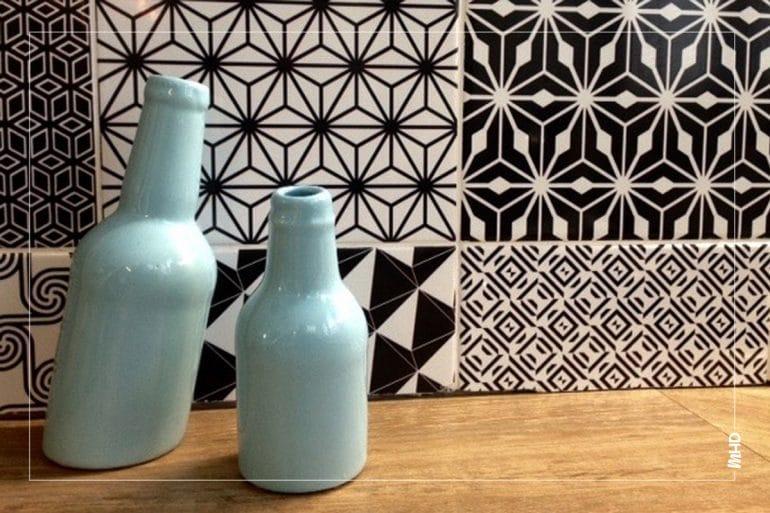 Zoom sur deux vases bleu turquoise assez clair sur fond de mosaïque de carrelage dans les tons black/white.