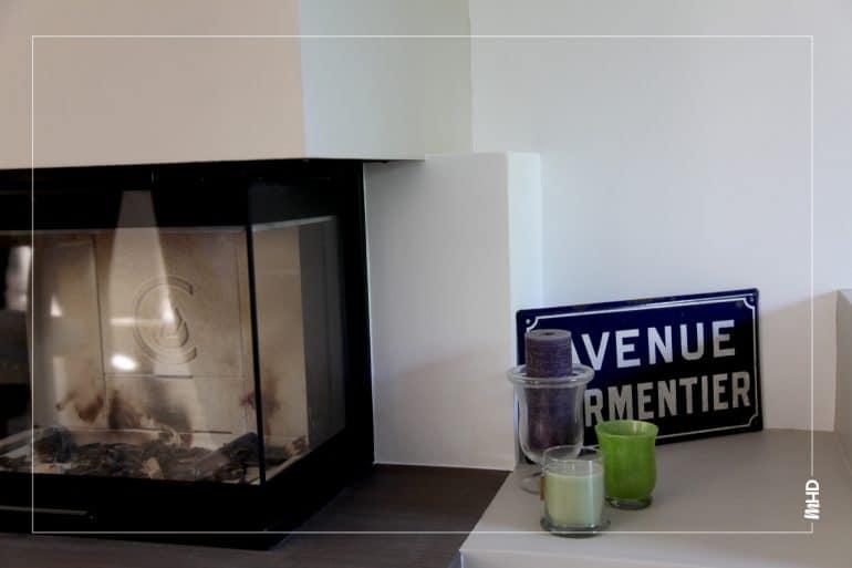 On observe sur cette photo une belle cheminé au coeur du salon avec un contraste noir et blanc, des détails urbain tel que le panneau d'affichage de la rue avenue Parmentier et de belles bougies.