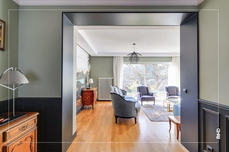 Le couloir est encadré de peinture noire. Devant, l'espace séjour avec 2 fauteuils classique