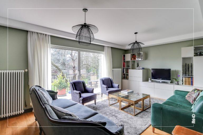 Espace séjour avec un canapé gris, 2 fauteuils gris classiques et un meuble tv blanc laqué contemporain. Au centre, une table basse en verre et au plafond 2 suspensions filaires noires