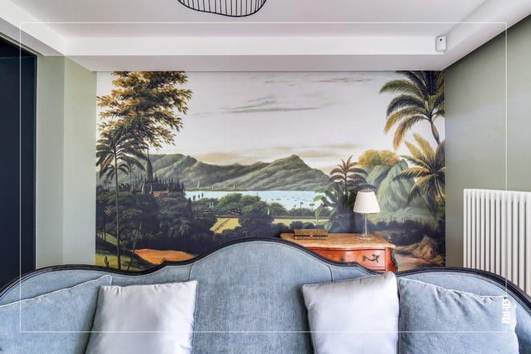 Dossier de canapé gris, derrière lit, papier peint panoramique de paysage peint à la main