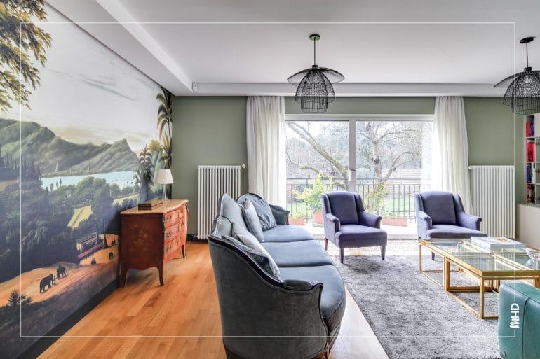 Vue du salon depuis le couloir, un canapé gris et 2 fauteuils classiques. Au fond, une grande baie vitrée avec vue dégagée