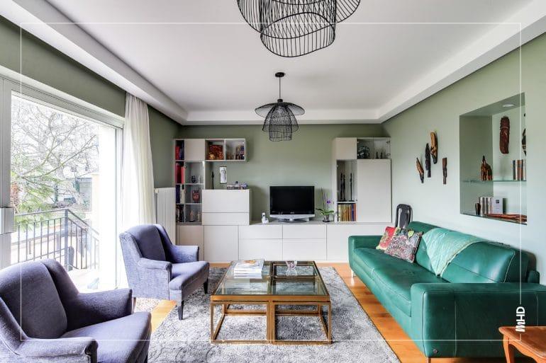 Espace séjour avec un canapé en cuir vert, 2 fauteuils gris classiques qui lui font face, une table basse en verre au centre. Au-dessus, suspension filaire noire et au fond une composition de meubles contemporains blanc laqué