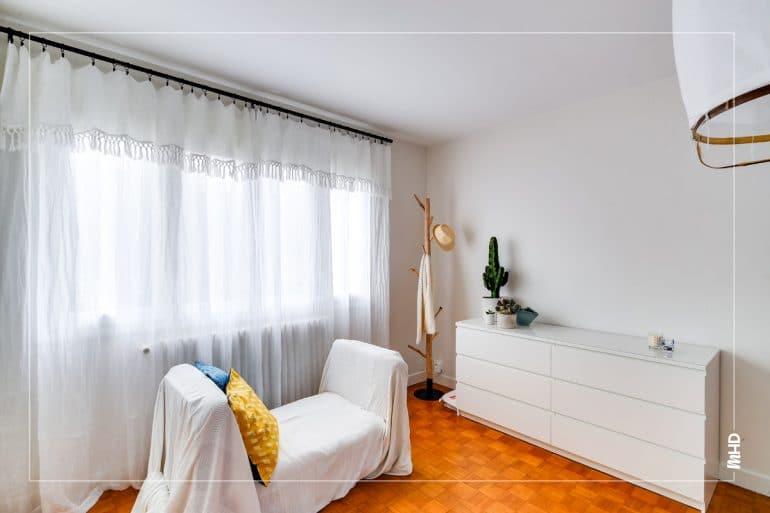 Au premier plan, une banquette recouverte d'un drap blanc. Derrière, une grande commode blanche avec des cactus en pot posés dessus. A sa gauche, un porte manteau en bois. Du parquet bois au sol et les murs et les plafonds sont blancs