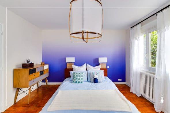 Lit 2 places avec du linge de lit blanc et des coussins blancs. Derrière le lit, un grand panneau de peint peint est posé sur le mur en guise de tête de lit. Le papier peint a un effet tie and dye, allant du bleu outremer en bas au blanc en haut