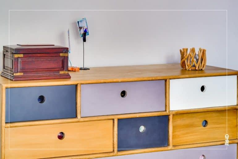 Une commode en bois avec des tiroirs bleus, blanc et bois. Sur la commode, des petits objets de décoration