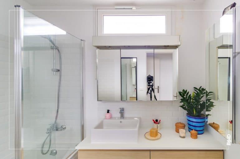 Grande vasque de salle de bains blanche avec meuble en bois. Meuble haut armoire à pharmacie avec portes miroir. Crédence en carrelage métro blanc